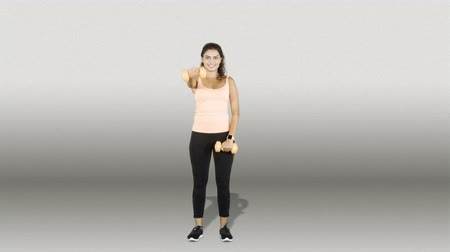 fulllength : Full body of young Asian woman exercising with two dumbbells while wearing sportswear in the studio. Shot in 4k resolution with gray background