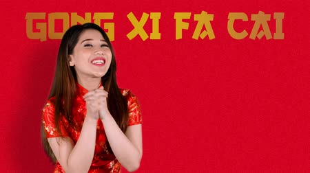 gong : Cheerful Asian woman congratulate Happy Chinese New Year or Gong Xi Fa Cai while wearing red cheongsam clothes. Shot in 4k resolution
