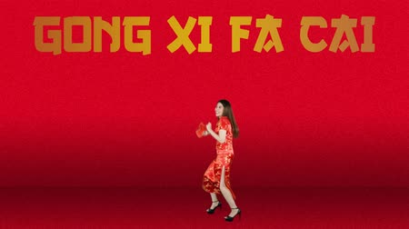 gong : Joyful pretty Asian woman celebrating Chinese New Year while wearing red cheongsam clothes and dancing with Gong Xi Fa Cai text background. Shot in 4k resolution
