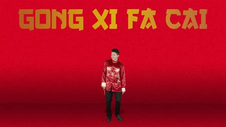 gong : Cheerful Asian man celebrating Chinese New Year while dancing and wearing red cheongsam clothes with Gong Xi Fa Cai text background. Shot in 4k resolution Stock Footage