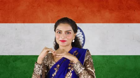 vlajky : Happy Indian woman dancing in front of Indian national flag while wearing saree clothes. Shot in 4k resolution