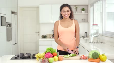 brokkoli : Pretty Asian woman smiling at the camera while slicing vegetables and fruits in the kitchen at home. Shot in 4k resolution Stock mozgókép