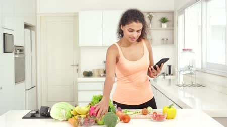 indonésio : Young woman holding a mobile phone and looking the recipe while preparing vegetables and fruits in the kitchen at home. Shot in 4k resolution