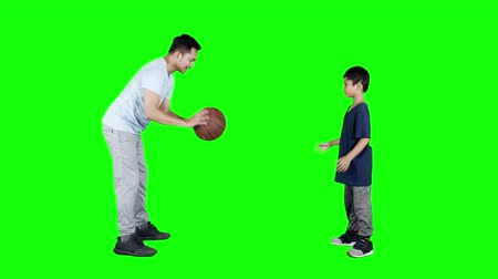 passar : JAKARTA, Indonesia - January 08, 2019: Little boy and his father playing catching and throwing basketball. Shot in 4k resolution with green screen background