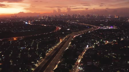 toll : JAKARTA, Indonesia - January 04, 2019: Beautiful aerial view of sunset with landscape of Becakayu toll road and residential houses in Jakarta. Shot in 4k resolution