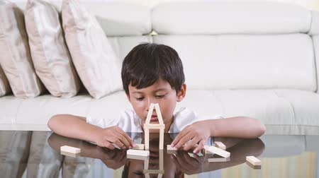 pillow block : Asian cute boy playing wooden blocks on the table in the living room at home. Shot in 4k resolution Stock Footage