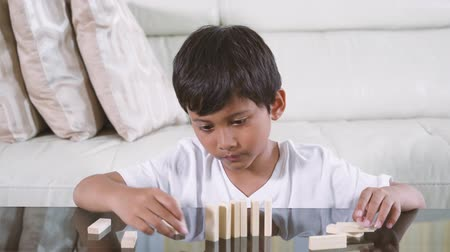 pillow block : Asian little boy playing wooden blocks alone in the living room at home. Shot in 4k resolution Stock Footage