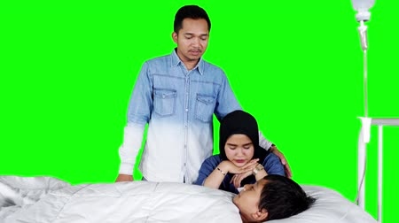 beside : Young parents sitting beside their sick son lying on the hospital bed. Shot in 4k resolution with green screen background