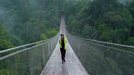 サスペンション : Young woman walking on the Situ Gunung Suspension Bridge while enjoying the forest landscape in Sukabumi, West Java, Indonesia. Shot in 4k resolution