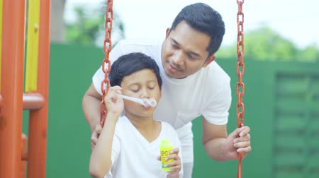 asian family : Cute little boy playing soap bubbles with his father while sitting on a swing at playground. Shot in 4k resolution