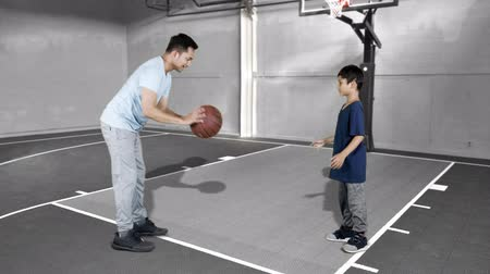 slintání : JAKARTA, Indonesia - January 08, 2019: Young man teaching his son to play basketball at indoors basketball court. Shot in 4k resolution
