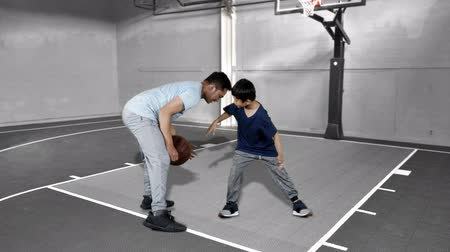 slintání : Attractive little boy playing basketball with his father at basketball court. Shot in 4k resolution