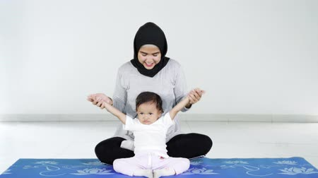colchão : Happy young muslim mother teaching her little daughter to meditation while sitting on yoga mat at home. Shot in 4k resolution