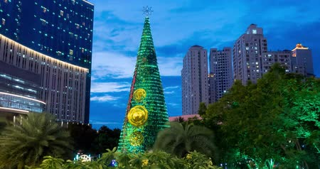 new town : JAKARTA, Indonesia - January 04, 2019: Beautiful time lapse of Christmas tree with lights outdoors at dusk in Jakarta city. Shot in 4k resolution Stock Footage