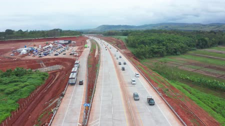 trans : Semarang, Central Java  Indonesia - January 11, 2019: Aerial view of Trans-Java Toll Road with fast traffic and an under construction rest area. Shot in 4k resolution Stock Footage