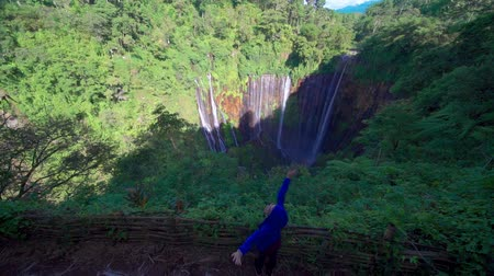 wanderlust : Happy woman enjoying freedom at Tumpak Sewu waterfalls also known as Coban Sewu waterfalls at Lumajang, East Java, Indonesia Stock Footage