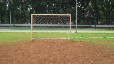 turf : Empty goalpost at the football field with brown land. Shot in 4k resolution