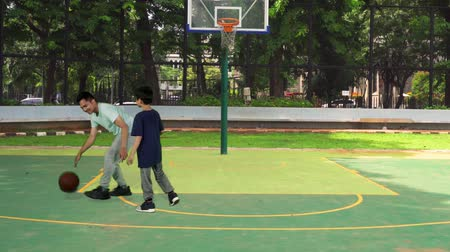 outdoor : Young father playing basketball with his son on the outdoor basketball court. Shot in 4k resolution