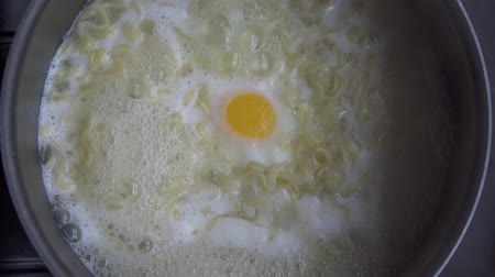kavurma : Closeup of instant noodles boiling in a pan with egg. Shot in 4k resolution