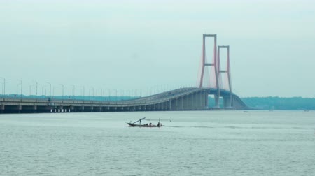 madura : Landscape of Madura Strait with boat and Suramadu Bridge background at Surabaya city, East Java, Indonesia. Shot in 4k resolution