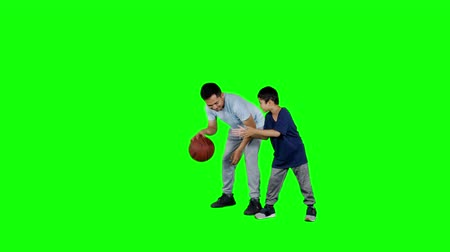 basquetebol : Young man playing basketball with his son in the studio. Shot in 4k resolution with green screen background