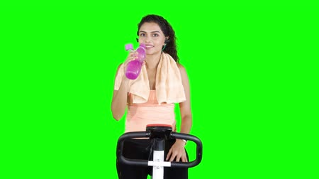 paquistão : Pretty woman drinking water from bottle while riding exercise bike. Shot in 4k resolution with green screen background Stock Footage