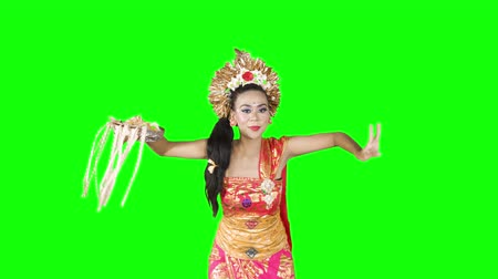vítejte : Attractive female balinese dancer showing a dance in the studio. Shot in 4k resolution with green screen background