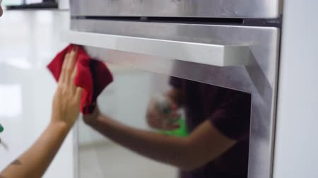 servis : Closeup shot of woman hand cleaning an oven with a microfiber cloth and spray in the kitchen at home. Shot in 4k resolution