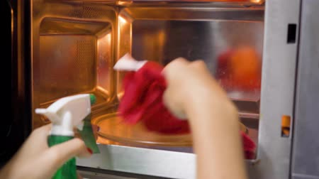 microonda : Woman hand cleaning a microwave oven with a cloth and spray. Shot in 4k resolution Stock Footage