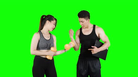 vzpírání : Personal trainer helping a beautiful woman exercising with dumbbells. Shot in 4k resolution with green screen background