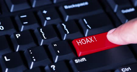 evidência : Human finger pressing Hoax button on the computer keyboard. Shot in 4k resolution