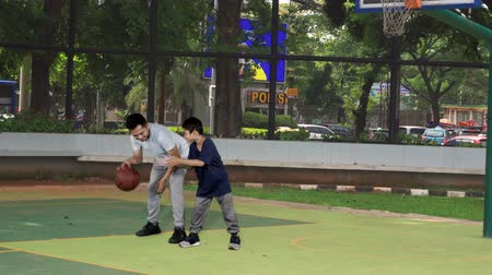 comprimento total : Happy young man and his son playing basketball together on the outdoor basketball court. Shot in 4k resolution