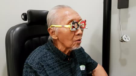optyk : Old man doing eyes test while wearing optometrist trial frame in the ophthalmology clinic. Shot in 4k resolution