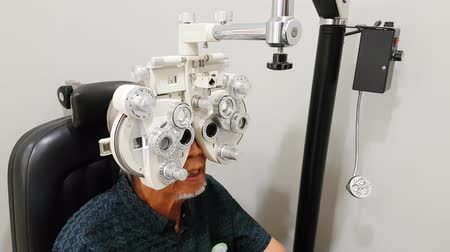 optyk : Old man examining his eyes with optometrist trial frame in ophthalmology clinic. Shot in 4k resolution