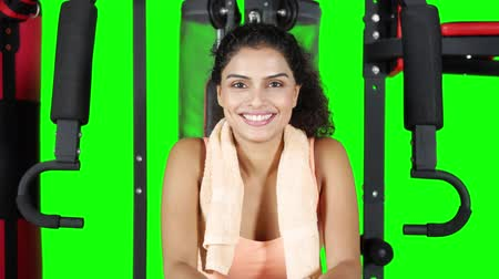 解決 : Attractive fitness woman smiling at the camera while sitting on the gym machine. Shot in 4k resolution with green screen background