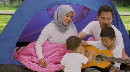 namiot : Happy muslim family with two children enjoying holiday while playing a guitar in the camping tent at the park. Shot in 4k resolution