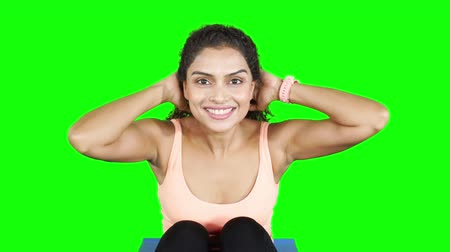 chroupat : Beautiful fitness woman exercising by doing sit ups on yoga mat. Shot in 4k resolution with green screen background