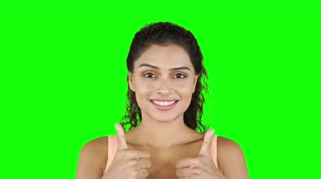 paquistão : Pretty fitness woman smiling at the camera and showing thumbs up. Shot in 4k resolution with green screen background