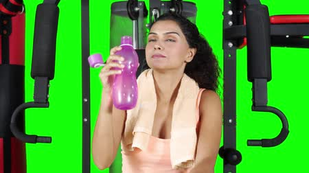 ağır çekimli : Healthy fitness woman drinking water from a bottle and smiling at the camera while sitting on a gym machine. Shot in 4k resolution with green screen background