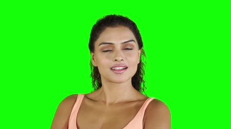 hispánský : Slow motion of a pretty fitness woman looking and smiling at the camera while standing in the studio. Shot with green screen background