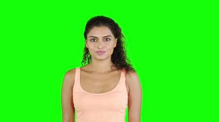 paquistão : Slow motion of attractive fitness woman showing thumbs up and smiling at the camera with green screen background. Shot in 4k resolution