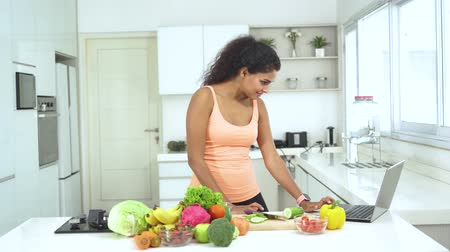 brócolis : Young woman slicing vegetable and fruit to make salad while using a laptop in the kitchen at home. Shot in 4k resolution