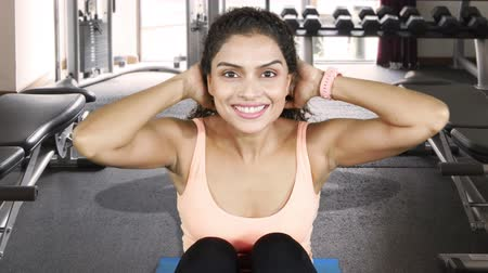 chroupat : Fitness woman exercising by doing sit-ups while smiling at the camera in fitness center. Shot in 4k resolution