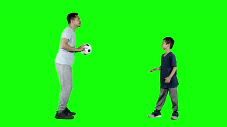 вратарь : Young man teaching his son to throw and catching a soccer ball. Shot in 4k resolution with green screen background Стоковые видеозаписи