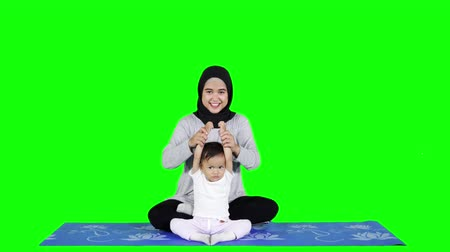 ислам : Happy young mother teaching her daughter to practice yoga exercise in studio. Shot in 4k resolution with green screen background Стоковые видеозаписи