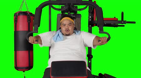 saç bantı : Overweight man doing exercise to lose weight on gym machine. Shot in 4k resolution with green screen background
