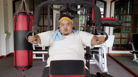 saç bantı : Overweight man exercising with a gym machine to lose weight in fitness center. Shot in 4k resolution Stok Video