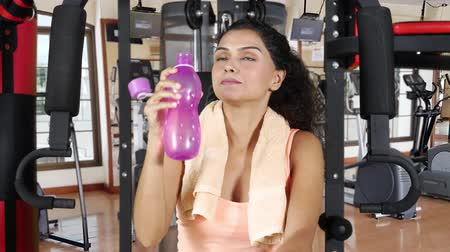 ivászat : Pretty young woman drinks water while sitting on gym machine and smiling at the camera in fitness center. Shot in 4k resolution