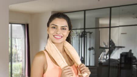 paquistão : Beautiful fitness woman smiling at the camera while holding a towel on her neck in fitness center. Shot in 4k resolution