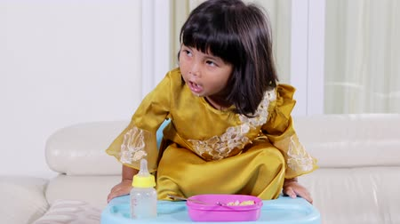 indonesian : Attractive little girl having lunch while sitting on high chair at home. Shot in 4k resolution